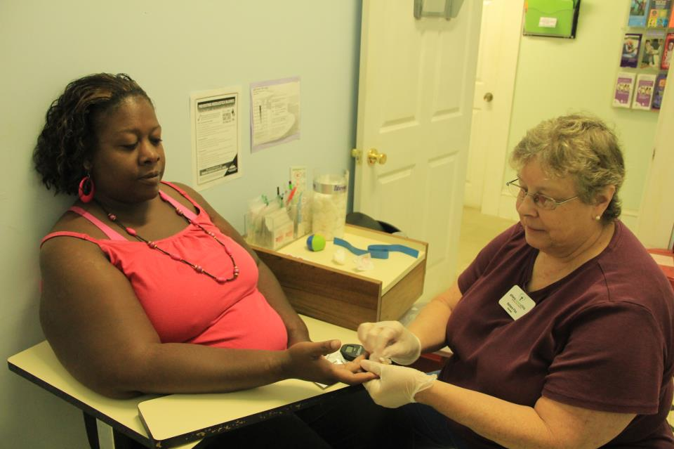 Barbara Flick, a long time volunteer at the clinic prepares a patient for an HbA1C blood glucose test.